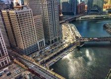Opinión de alto ángulo del tren del EL que pasa sobre las aguas que brillan de la mañana del río Chicago en marzo en invierno foto de archivo libre de regalías