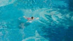 Opinión de alto ángulo el adolescente asiático que nada al aire libre en piscina azul Imágenes de archivo libres de regalías