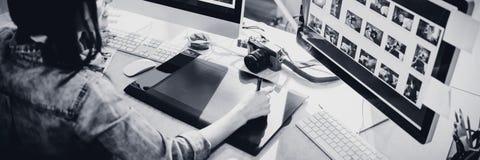 Opinión de alto ángulo el diseñador gráfico usando la tableta de gráficos imagen de archivo libre de regalías