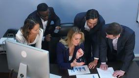 Opinión de alto ángulo el equipo creativo que se coloca alrededor de la tabla que discute ideas del negocio almacen de metraje de vídeo