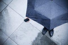 Opinión de alto ángulo el hombre de negocios que sostiene un paraguas y que mira su teléfono en la lluvia imágenes de archivo libres de regalías