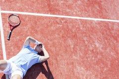 Opinión de alto ángulo el hombre maduro decepcionado con la cabeza en manos mientras que miente por la estafa de tenis en corte d fotografía de archivo libre de regalías