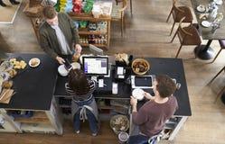 Opinión de alto ángulo el hombre que paga sobre contador en una cafetería fotos de archivo libres de regalías