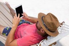 Opinión de alto ángulo el hombre que usa la tabla digital mientras que miente en hamaca Imagenes de archivo