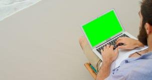 Opinión de alto ángulo el hombre usando el ordenador portátil en la playa 4k almacen de video