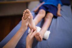 Opinión de alto ángulo el muchacho que miente en la cama que recibe masaje del pie de terapeuta de sexo femenino fotos de archivo libres de regalías