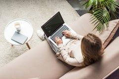 opinión de alto ángulo de la codificación femenina joven del promotor con el ordenador portátil fotografía de archivo libre de regalías