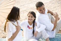 Opinión de alto ángulo la familia hispánica feliz en la playa Imagen de archivo libre de regalías
