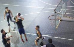 Opinión de alto ángulo la gente asiática joven que juega al baloncesto al aire libre en la noche imagen de archivo libre de regalías
