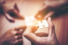 Opinión de alto ángulo de la mano de los empresarios que soluciona el rompecabezas encendido fotos de archivo libres de regalías