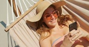 Opinión de alto ángulo la mujer caucásica que usa el teléfono móvil en una hamaca en la playa 4k metrajes