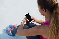Opinión de alto ángulo la mujer que usa el teléfono móvil en la playa imagenes de archivo
