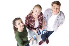 Opinión de alto ángulo los amigos adolescentes que sostienen smartphones con el logotipo del facebook Fotografía de archivo