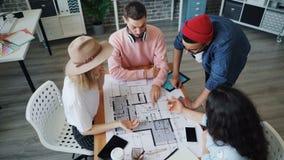 Opinión de alto ángulo los arquitectos jovenes que hablan el dibujo en hacer del plan entonces alto-cinco almacen de metraje de vídeo