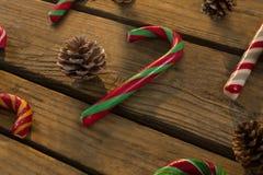 Opinión de alto ángulo de los bastones de caramelo y de los conos del pino en la tabla Imagenes de archivo