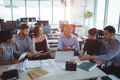 Opinión de alto ángulo los colegas creativos del negocio que discuten alrededor del escritorio fotos de archivo libres de regalías