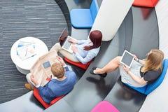 Opinión de alto ángulo los hombres de negocios que se sientan en pasillo de la oficina Foto de archivo libre de regalías