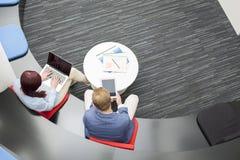 Opinión de alto ángulo los hombres de negocios que usan tecnologías en oficina Imagen de archivo libre de regalías