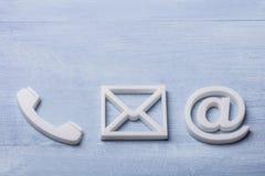 Opinión de alto ángulo de los iconos del teléfono, del correo electrónico y de los posts imagenes de archivo