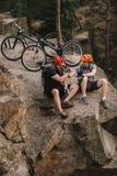 opinión de alto ángulo los motoristas de ensayo jovenes que se relajan en el acantilado rocoso después de paseo y de sacudir imagenes de archivo