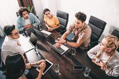opinión de alto ángulo los socios comerciales multiculturales que tienen reunión en la tabla con los ordenadores portátiles en mo imágenes de archivo libres de regalías