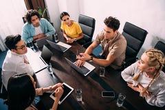 opinión de alto ángulo los socios comerciales multiculturales que tienen reunión en la tabla con los ordenadores portátiles en mo fotografía de archivo libre de regalías