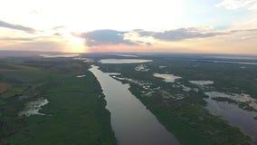 Opinión de alto ángulo sobre un río en la puesta del sol 4K almacen de video