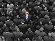 Opinión de alto ángulo un hombre de negocios que se coloca en medio de empresarios Foto de archivo libre de regalías