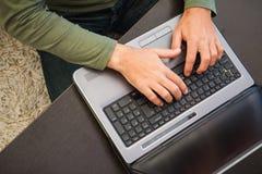 Opinión de alto ángulo un hombre que mecanografía en el ordenador portátil Imagen de archivo libre de regalías