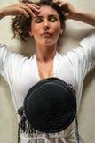 Opinión de arriba del retrato una mujer joven hermosa que coloca en su chalet costoso con el bolso luxuty del pitón Tenga pelo ri imagen de archivo