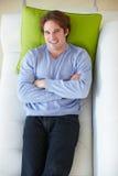 Opinión de arriba el hombre que se relaja en el sofá foto de archivo libre de regalías