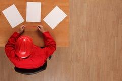 Opinión de arriba el trabajador en papeles de la lectura del uniforme y del casco de protección del rojo imagen de archivo
