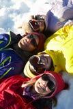 Opinión de arriba la familia adolescente que miente en nieve Fotos de archivo
