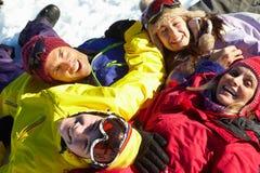 Opinión de arriba la familia adolescente que miente en nieve Foto de archivo