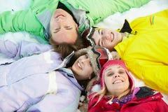 Opinión de arriba la familia adolescente que miente en nieve Imagenes de archivo