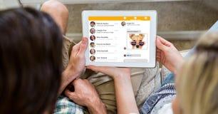 Opinión de arriba la gente que usa la tableta digital mientras que se sienta en casa Foto de archivo