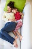 Opinión de arriba la madre y la hija que se relajan en el sofá fotos de archivo libres de regalías