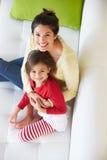 Opinión de arriba la madre y la hija que se relajan en el sofá foto de archivo libre de regalías