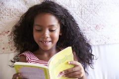 Opinión de arriba la muchacha que miente en el libro de la cama y de lectura foto de archivo libre de regalías