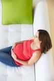 Opinión de arriba la mujer embarazada que se relaja en el sofá imagenes de archivo