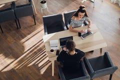 Opinión de arriba la mujer joven que lleva un smartwatch que trabaja en su ordenador portátil en un café La visión superior tiró  foto de archivo
