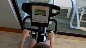 Opinión de arriba la persona que usa la bicicleta estática en gimnasio almacen de video