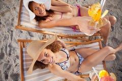 Opinión de arriba las mujeres jovenes sonrientes que aumentan sus cócteles Imagen de archivo libre de regalías