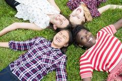 Opinión de arriba los amigos de adolescente que mienten en hierba Fotos de archivo libres de regalías