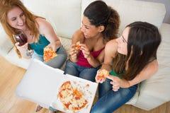 Opinión de arriba los amigos felices que comen la pizza con el vino en el sofá Imagen de archivo libre de regalías