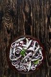 Opinión de arriba los espadines salados adobados con los anillos de cebolla roja, semillas de coriandro en una placa de la loza d fotografía de archivo libre de regalías