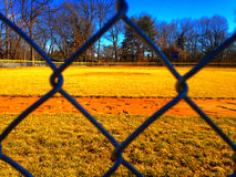 Opinión de campo de béisbol del cobertizo a través de la cerca imagen de archivo