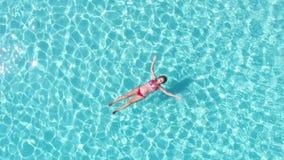 Opinión de giro aérea una mujer atractiva que flota en el mar cristalino almacen de metraje de vídeo