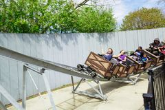 Opinión de invitación los niños, los niños felices y los adultos disfrutando de su tiempo libre montando en los carros de una min Fotografía de archivo