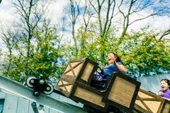 Opinión de invitación que sorprende los niños felices, niños que disfrutan de su tiempo libre montando en los carros de una mina  Imágenes de archivo libres de regalías